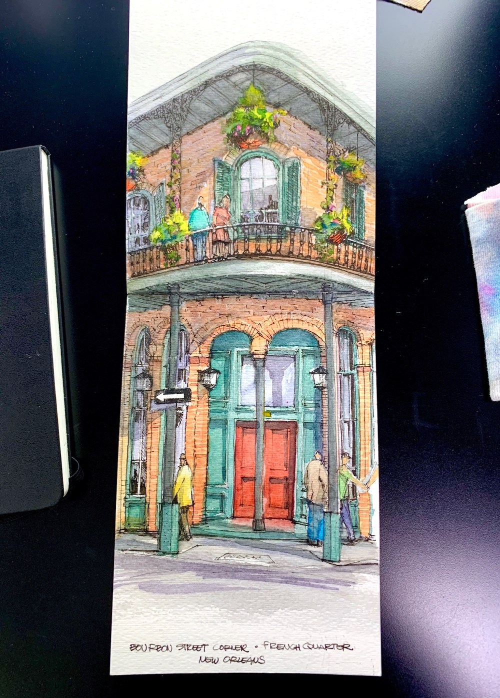 Strathmore Sketchbook over black desk. Brick building with red door watercolor and ink sketch