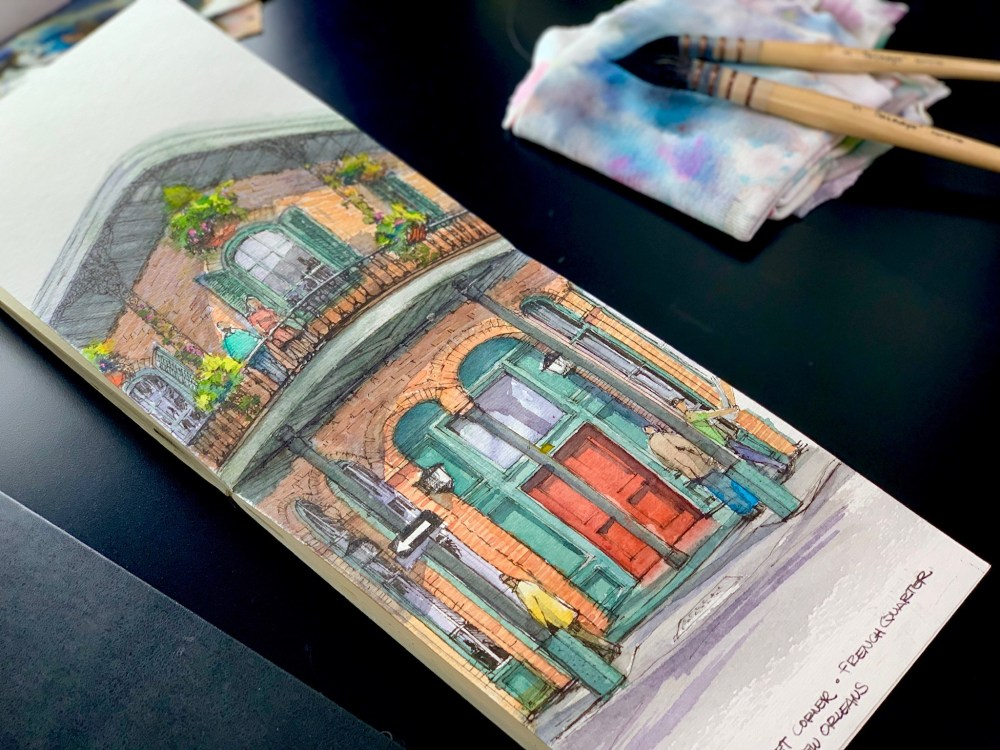 Moleskine Sketchbook over black desk with brushes. Brick building with red door watercolor and ink sketch