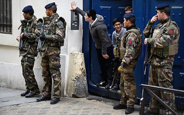 Illustrative: Children look out from a doorway as armed soldiers patrol outside a school in the Jewish quarter of the Marais district in Paris, January 13, 2015. (Jeff J. Mitchell/Getty Images/via JTA)