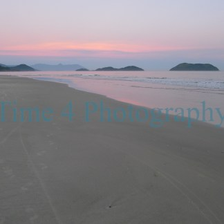 A beach in Brazil at sunset. The sand is still golden and the pink colored clouds reflect on the mirror-like sea water. At this hour, the beach is deserted.