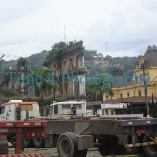 Abandoned ruined buildings at downtown Santos, being invaded by a lush vegetation. In the foreground there are some big trucks