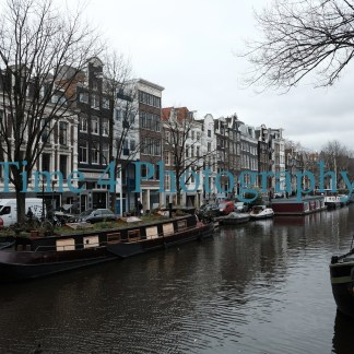 Amsterdam canal at daytime, depiciting houses in the background and boats anchored at its margins. The canal water is dark and sky overcast.