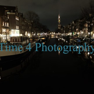 Canal in Amsterdam at night, the lights of houses and a church far away reflect on the dark water and some boats are moored at the left margin.