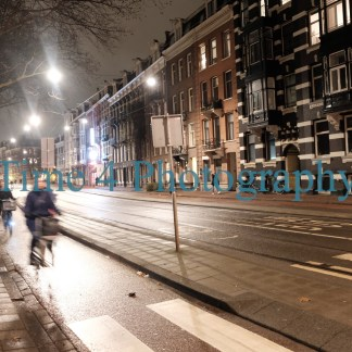 A cold and rainy winter night in Amsterdam, the street is almost deserted, a few ciclists are aproaching on the bicycle lane.