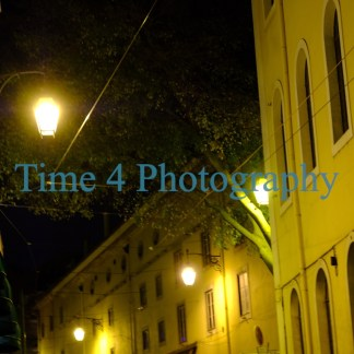 Brightly lit streetlamps along an alley in Lisbon