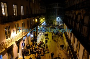 Many people on a street with restaurants and cafes at night in Lisbon,Portugal