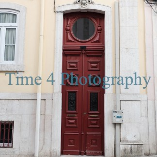 A red-brown door in Lisbon, Portugal, inserted in a yellow facade