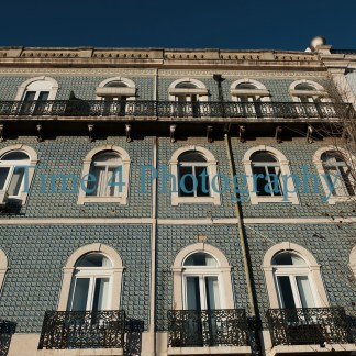 A typical facade of blue tiles in Lisbon, Portugal, with big white window frames