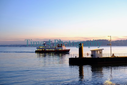 The Tejo riverat sunset in Lisbon,Portugal, with a boat arriving at a small pier