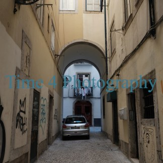 An old narrow alley in Lisbon, on the walls on both sides there are graffitis and in the background a car is parket under an arch.