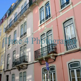 A row of old buildings in Lisbon, with balconies on the facades. The buildings are the colors pink, yellow and beige, and the sky is very blue.