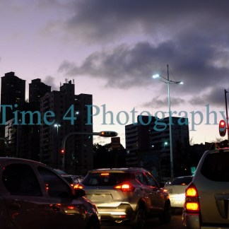Skyline of buildings at dusk in Salvador, Brasil, with lighted car taillamps in the foreground. Afar some lights go on in the buildings.