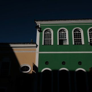 Yellow and green colonial buidlings, in strong colors and white window sills, against a dark blue sky in Salvador da Bahia in Brasil.