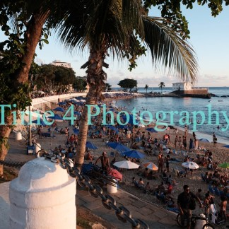 At the end of the day, many people relaxing on a beach in the city of Salvador da Bahia in Brazil.Some sunshades are still open and the sea es light blue.