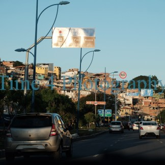 An urban slum in Salvador da Bahia, Brasil, built on a low hill, as seen from a car riding on an avenue right below the slum.