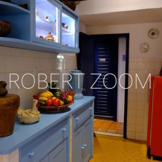A small part of a nice little kitchen with light blue furnitture and a red refrigerator. On the table there is a big choice of brazilian tropical fruits.