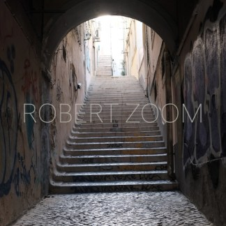 An old passage in Lisbon,Portugal. Its rounded ceiling and walls are covered with grafitti and steep stairs lead to the higher part of town.