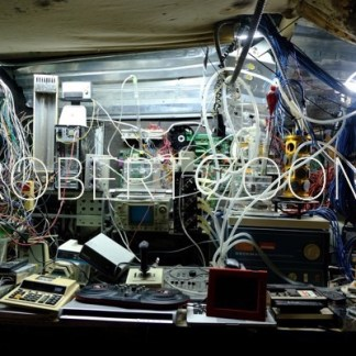 A lot of old electronic devices iand cables in disarray, set on a table and hanging from the walls
