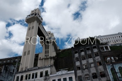 The famous Lacerda Elevator, in the lower city of Salvador da Bahia in Brazil, as seen from below, against a blue sky with white clouds.