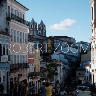 A narrow street in the old city of Salvador da Bahia, Brasil, showing colonial houses and churches. Many people are walking up and down.