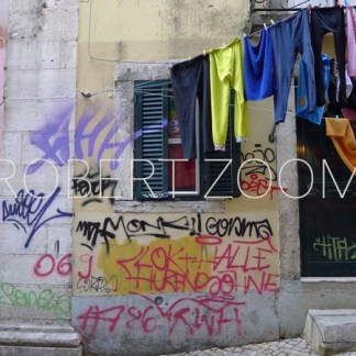 In front of a narrow house in Lisbon, clothes in various colors hang from windows on the street.The walls are covered with grafitti.