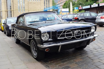 Front view of a black 1966 convertible Mustang, market at the curb of a cobblestone street. On the background some other cars and a building