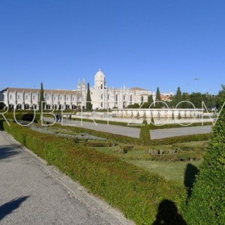 The famous Monastery of Jeronimos seen in the background, with a green lawn in the foreground and a blue sky