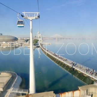 On a sunny day in Lisbon, this picture shows a cable car riding over Nations Park. The Tejo river water is blue, as well as the sky above.