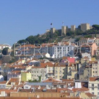 Saint George Castle in Lisbon, Portugal, located on a hill and on the foreground there are many houses