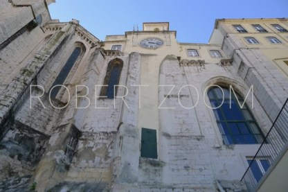 Old church wall in Lisbon Portugal, very high and narrow windows and a clock at the top of it