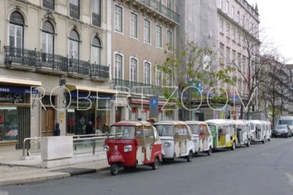 Parked along the curb of an avenue in Lisbon, a line of TucTucs, very small vehicles with 3 wheels, are waiting for new passangers.