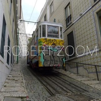 In a narrow street of Lisbon, an old streetcar with the front covered in graphitty