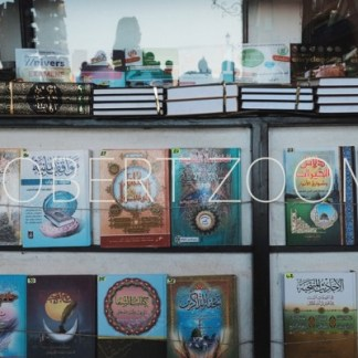 This picture shows a bookstore window in Marrakech, Morocco, displaying several titles in arabic language and richly decorated book covers.