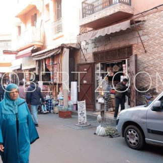People walking on a busy street with shops in Marrakech, Morocco