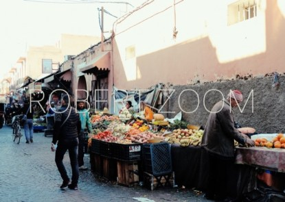A seller of groceries displaying his products in boxes on the sidewalk of a steet in Marrakech, Morocco