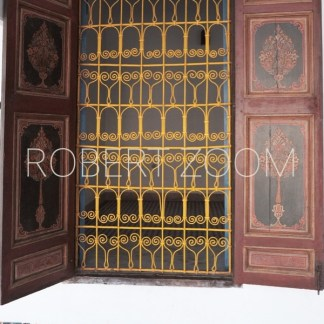 Wooden arabic window decorated with drawings and with a yellow grid