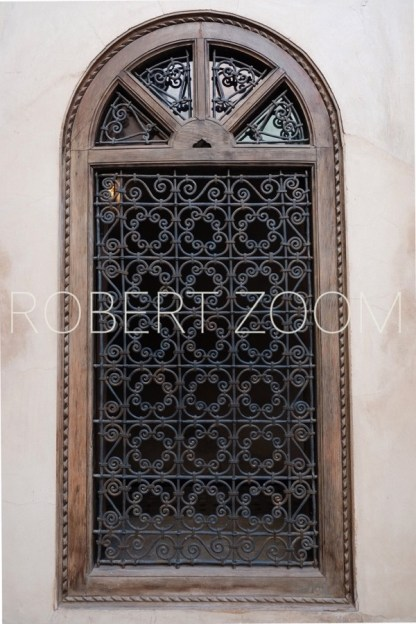 Wooden arabic window with a brown decorated grid, amid a white wall
