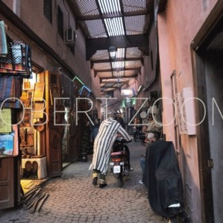 Covered alley in the Medina of Marrakesh in Morocco, showing some shops and a person pushing a motorbike on the cobblestone