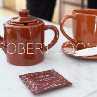 Brown teapot and cup and a tea bag envelope on a white table, in Marrakech, Morocco