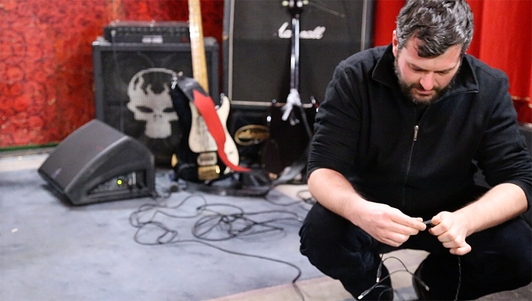 Bass player and lead vocalist of Duesenjaeger Tobi plugging in his bass destruction machine before the gig at Schokoladen