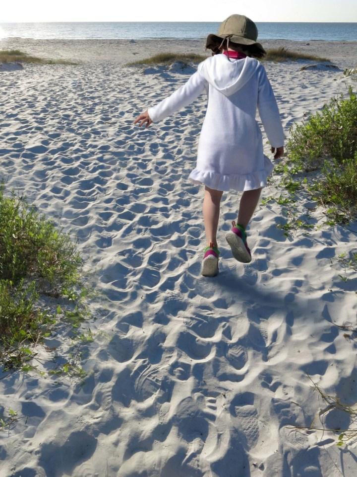 Robin Botie walks behind a joyful girl on the beach at Sanibel Island.