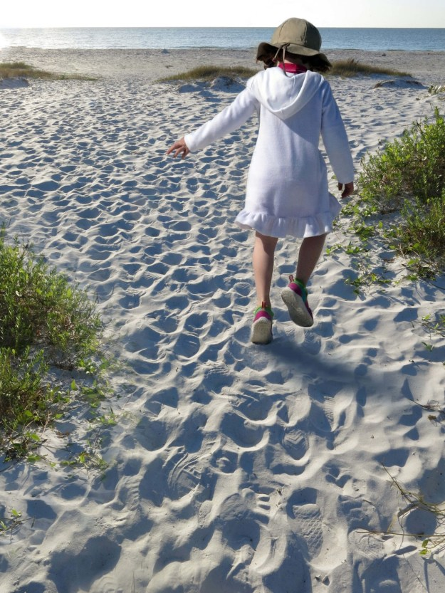 Robin Botie walks behind a joyful girl on the beach at Sanibel Island.