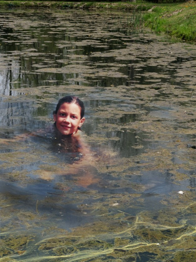 Staying Afloat -- Robin Botie in Ithaca, New York Photoshops daughter, Marika Warden, swimming in pond filled with algae.
