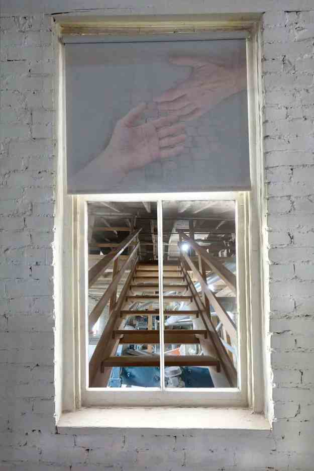 Robin Botie of Ithaca, New York, photoshops hands reaching out over a scene of brick wall and staircase.