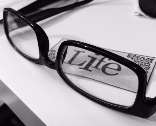 "Black frame glasses around the word ""Life"" - black and white photo"