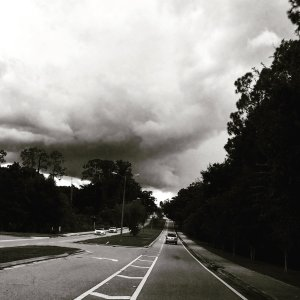 neighborhood road with story clouds and sky