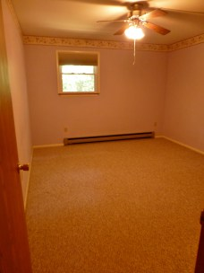 BEFORE: The view upon entering this upstairs bedroom is of the window wall. The room is painted a pale lavender color with a purple floral wallpaper border. It has the same cheap old shell molding for casing and baseboards, which gives the room a tired and dated feel. There's also a mottled Berber style carpet in the room, which we will be happy to remove!