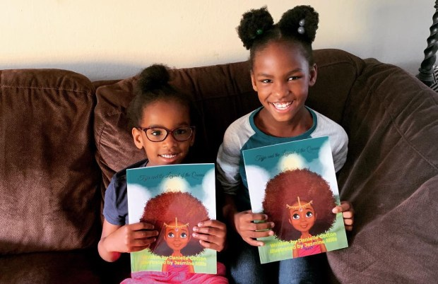 The adorable Sofia and Zoe with their mom's book, Tajja and the Legend of the Queens.