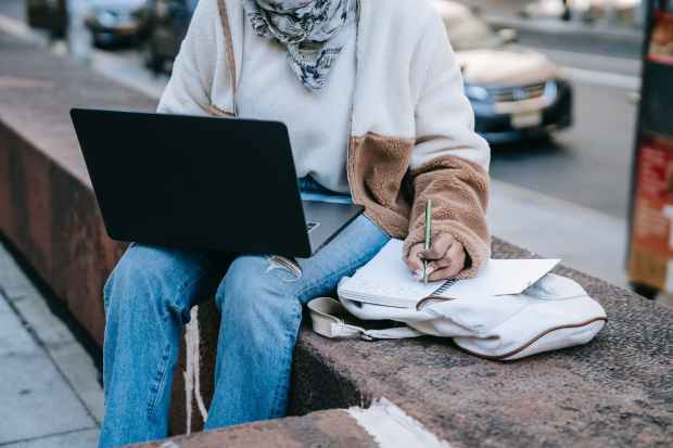 anonymous female using laptop and taking notes on street