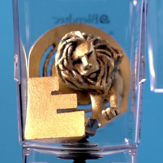 Een in plastic 3D-geprinte en 'vergulde' Effie Award en Lion Award samen in de blender vlak voordat deze wordt aangezet.